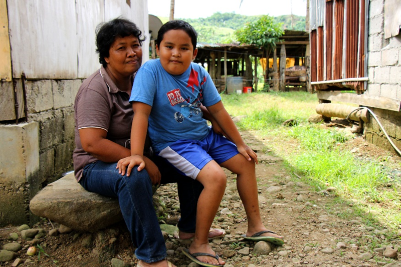 Kuvassa Leonora on nuorimman lapsensa kanssa heidän talonsa edustalla.