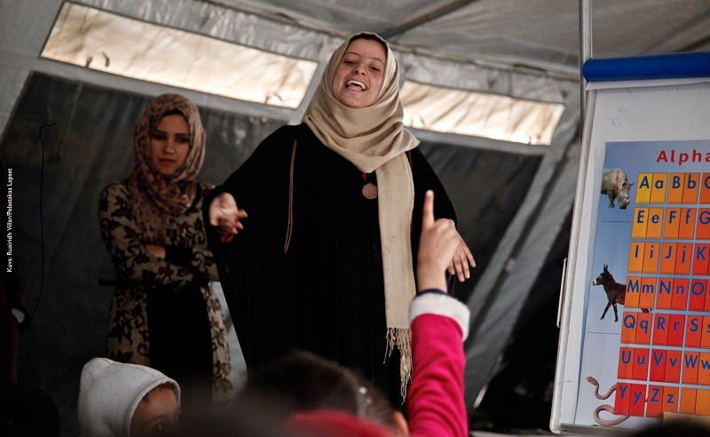"""November 20, 2016. Qayyarah, Iraq. Sabri*, one of Save the Children's teachers in Qayyarah Jad'ah camp, teaches a group of children. She is one of 13 female teachers hired by Save the Children from inside Qayyarah Jad'ah camp. The charity has set up tents to provide safe learning a play spaces for children fleeing the Mosul offensive. Sabri* fled a town south of Mosul after Iraqi army forces pushed ISIS fighters back. She says she spent more than two years under ISIS, almost entirely confined to her home. """"I want to save children from ignorance - it has been two years with ISIS, they have been trapped by ISIS, and children don't know how to read. I specialised in education at university and got this opportunity - so I want to take this chance to teach. """"It was very hard under ISIS and there was no studying. Families and everyone were facing hardship. It was very hard under ISIS and it just destroyed us, it destroyed our families, it crushed our futures. It reached a point when you came and talked to children about schools and they wouldn't know what a school was. Especially the ones who were never enrolled to begin with. It was very hard. """"Before ISIS came I was a teacher and I was studying. And then when ISIS came we just sat at home doing nothing. The situation now is different, it's got better, psychologically I feel better. We were depressed, we were feeling like it's hopeless, that we'd never get education back. Now hope is back. """"The difference is quite big, The children now are quite happy about the new schools. They're even happier and more excited than we are. So they come early, they come earlier than the start time every day. They feel they are being taken care of."""""""