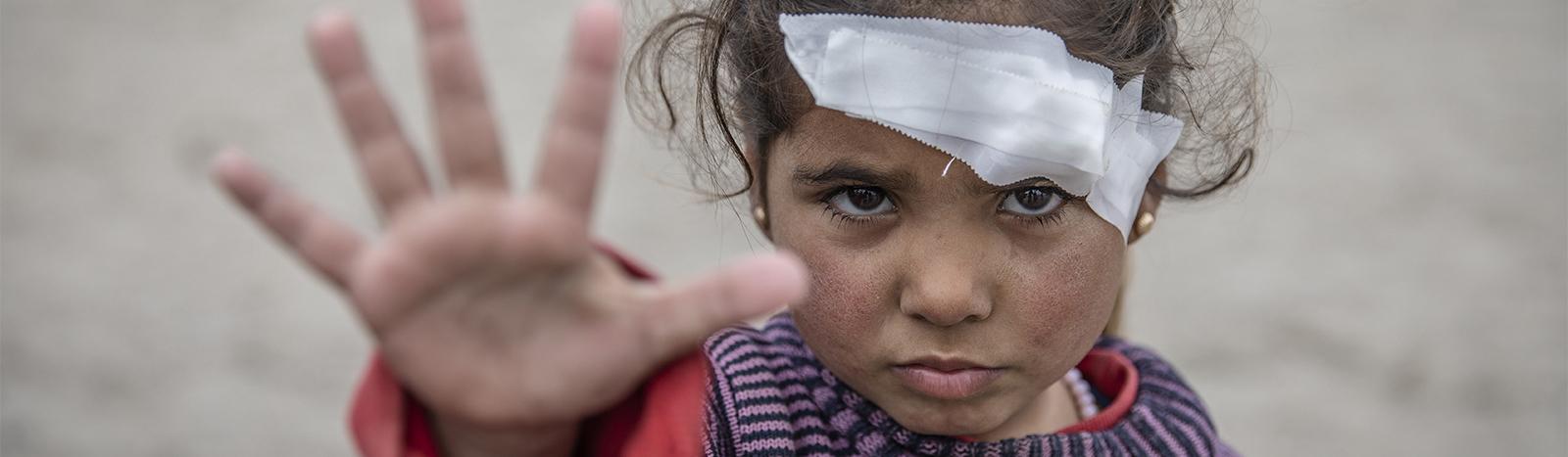 Lapsi näyttää stop-merkkiä kädellään sodalle.